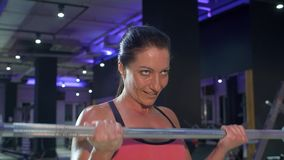 Woman pumping biceps. Woman doing bodybuilding exercise pumping biceps lifting barbell. Athlete in the gym. Fitness, sport, and training concept stock video footage