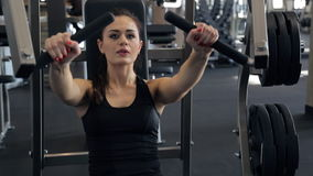 Woman pumping chest muscles on special equipment in sport gym stock footage
