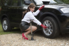 Woman pumping up car tyre Royalty Free Stock Images