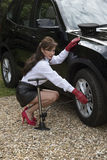 Woman pumping up car tyre Royalty Free Stock Photography