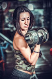 Woman pumping up muscules with dumbbells Stock Photos