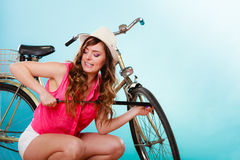 Woman pumping up tire tyre with bike pump. Stock Photos