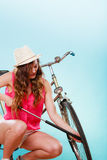 Woman pumping up tire tyre with bike pump. Royalty Free Stock Image