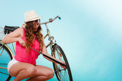 Woman pumping up tire tyre with bike pump. Royalty Free Stock Photo