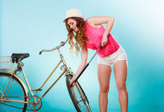 Woman pumping up tire tyre with bike pump. Royalty Free Stock Photos