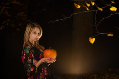 Woman with pumpkin in dark forest. And magic glow Royalty Free Stock Photo