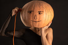 Woman with a pumpkin on head and electric cord Stock Photo