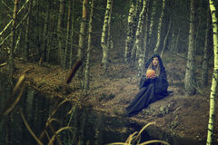 Woman with pumpkin sitting near water Royalty Free Stock Images