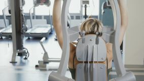 Woman pumps back muscles in the gym. The camera shoots from back. Young woman wearing sporty outfit is in the gym. Sporty young woman sits at the training stock video