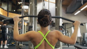 Woman pumps iron in Fitness-station. View from her back. stock video