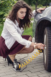Woman pumps up her car tire Stock Photo