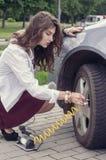 Woman pumps up her car tire Stock Photos
