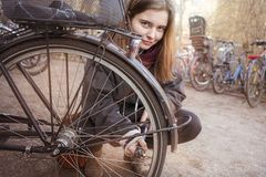 Woman pumps up the tires of her bike royalty free stock photo