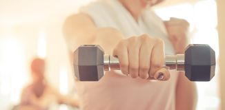 Woman punched out dumbbell to the camera. Woman punched out weight dumbbell to the camera Stock Photography