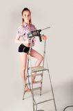 Woman with puncher on ladder Stock Images