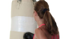 Woman Punching Heavybag. Woman working out with a heavybag. Studio shot over white.n stock video