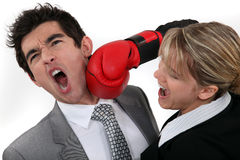 Woman punching her colleague. Woman punching her hard-headed colleague Royalty Free Stock Photos