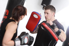 Woman punching pads with trainer Stock Photos