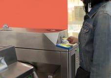 Woman punching ticket in machine to entering at metro station Stock Image