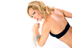 Woman punching wall in bra. An attractive blonde woman is looking over her shoulder at viewer as her fist rests on white wall Stock Image