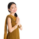Woman in Punjabi clothes greeting. Young mixed race Indian Chinese girl in traditional punjabi dress greeting gesture, standing isolated on white background Stock Photos