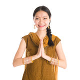 Woman in Punjabi dress greeting. Young mixed race Indian Chinese girl in traditional punjabi dress showing greeting gesture, standing isolated on white Royalty Free Stock Images