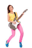Woman punk rock star playing. Full length of woman punk rock star playing an electric guitar over white background Royalty Free Stock Image