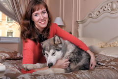 Woman with a puppy Malamute Royalty Free Stock Image