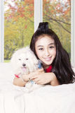 Woman and puppy playing in autumn season. Image of a happy young woman playing with a Maltese dog in the bedroom while smiling at the camera with autumn Stock Photos