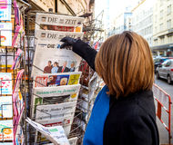 Woman purchases a Die Welt with Obama and Trump  newspaper from Stock Photography