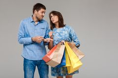 Woman with purchases, man holding last money over grey background. Stock Images