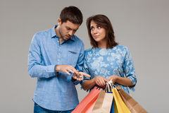 Woman with purchases, man holding last money over grey background. Royalty Free Stock Photography