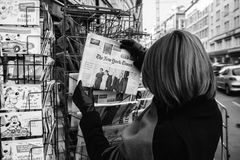 Woman purchases a New York Times with Obama and Trump newspaper Royalty Free Stock Image