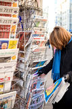 Woman purchases a Un Doigt French newspaper from a newsstand Stock Image