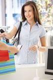 Woman purchasing clothes in shop. Getting back credit card, smiling at shop assistant Royalty Free Stock Photos