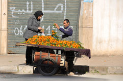 Woman purchasing tangerines from the man. Selling them in the street in Fes Royalty Free Stock Photos