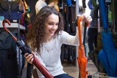 Woman purchasing umbrella in haberdashery shop Stock Image