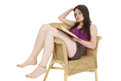Woman purple in chair reading stock images