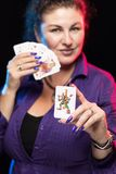 A woman in purple clothes holds a deck of cards and shows tricks. In a scenic light royalty free stock image