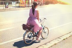 Woman in Purple Dress Riding on City Bicycle on Road Royalty Free Stock Photos