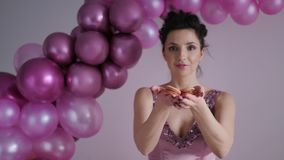 Woman in purple dress with sequins stretches his arms forward. With biscuits balls in the background stock footage