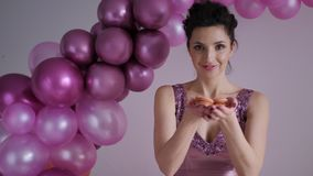 Woman in purple dress with sequins stretches his arms forward. With biscuits balls in the background stock video footage