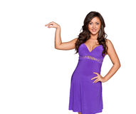 Woman in a purple dress. Shows that holding something in her hand and smiling at the camera, isolated on white background Stock Images