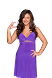 Woman in a purple dress. Shows that holding something in her hand and smiling at the camera, isolated on white background Royalty Free Stock Photography