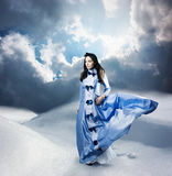 Woman in Purple Dress Walking on Winter Hills Royalty Free Stock Photo