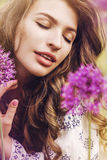 Woman among purple flowers in sunlight Royalty Free Stock Photos