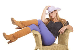 Woman purple hat sit chair. A woman sitting in her chair with her legs crossed showing off her boots Royalty Free Stock Photos