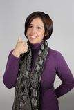 Woman with purple jacket and gray scarf. Makes a sign of approval royalty free stock images