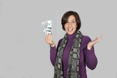 Woman with purple jacket and gray scarf. Portrait of a young woman holding a wad of hundred dollars to show his surprise stock images