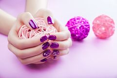 Woman with purple manicure holds a ball. On pink background royalty free stock image